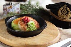 Meat pancake on black pan Stock Image