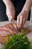 Meat and parsley. Woman slicing meat (ham Royalty Free Stock Images