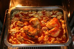 Meat and Pasta in the Oven. Baked chicken meat and pasta in the baking pan stock photography