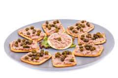 Meat pate with capers on crackers Royalty Free Stock Image