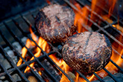 Meat Patties on Flaming Grill. Two meat patties are side by side on a grill with flames licking upward toward the meat royalty free stock photos
