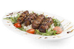 The meat Patty on the grill. With rice, tomatoes, arugula and sprinkled with sesame seeds Royalty Free Stock Photo