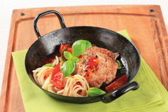 Meat patty with tomatoes and spaghetti Royalty Free Stock Photo