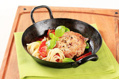 Meat patty with tomatoes and spaghetti Royalty Free Stock Image