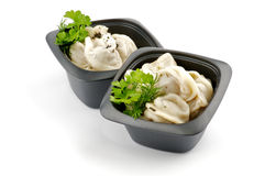 Meat pelmeni with sour cream and greens. In black bowls isolated on white background Royalty Free Stock Photography