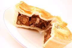 Meat Pie. A small lamb and rosemary pie, cut in half, on a white plate royalty free stock photos