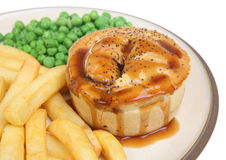 Meat Pie, Chips & Peas with Gravy. Freshly baked individual meat pie, decorated with poppy seeds and served with chips, peas and gravy Stock Photography