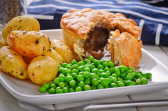 Meat pie with new potatoes and peas. Stock Image