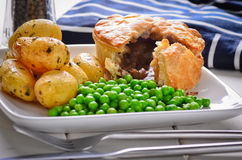 Meat pie with new potatoes and peas. Royalty Free Stock Photos