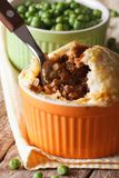 Meat pie in a pot on a background of green pea Vertical Stock Image