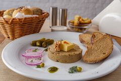 Meat pate. Meat pie served on a table with butter, onions and pickles stock photos