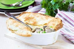 Meat pie with stew of chicken, mushrooms, peas, puff pastry Royalty Free Stock Images