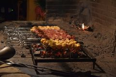 Meat pierced with skewers at the stake. Meat pierced with skewers at the roasting in the stake Royalty Free Stock Photos