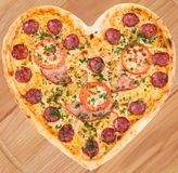 Meat pizza with ham in heart shape for valentine. Meat pizza with ham, salami, tomatoes and cheese topped with fresh Italian herbs in heart shape for valentine Royalty Free Stock Photography