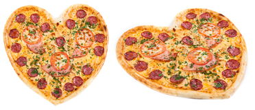 Meat pizza with ham, tomatoes and cheese topped with fresh Italian herbs in heart shape for valentine. Meat pizza with ham, salami, tomatoes and cheese topped Royalty Free Stock Photo