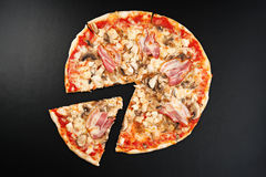 Meat pizza. With slice  on black background Royalty Free Stock Photography