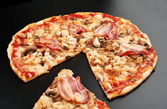 Meat pizza. With slice  on black background Stock Images