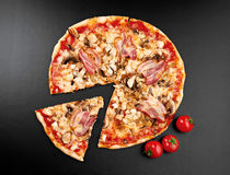 Meat pizza. With slice and tomatoes  on black background Royalty Free Stock Photo