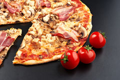 Meat pizza. With slice and tomatoes  on black background Royalty Free Stock Images