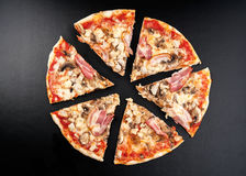 Meat pizza. With slices  on black background Stock Photos