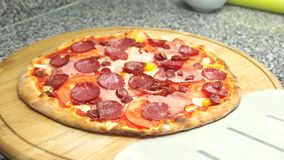 Meat pizza on wooden board. Ham, salami and pepperoni stock video footage