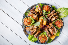 Meat plate with delicious pieces of meat, salad, lamb ribs, grilled vegetables, potatoes and sauce. Top view and wooden table Royalty Free Stock Photos