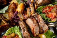 Meat plate with delicious pieces of meat, salad, ribs, grilled vegetables, potatoes and sauce. Close up image with selective focus Stock Photo