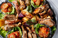 Meat plate with delicious pieces of meat, salad, ribs, grilled vegetables, potatoes and sauce. Top view Stock Photos