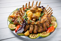 Meat plate with delicious pieces of meat, salad, ribs, grilled vegetables and potatoes on white wooden table Royalty Free Stock Photography