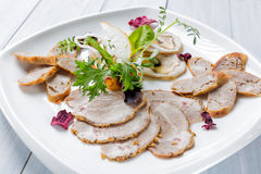 Meat plate with delicious pieces of sliced ham, sausage, herbs and meat with herbs. Close up with selective focus Royalty Free Stock Photography