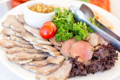 Meat plate with delicious pieces of sliced ham, sausage, meat, tomatoes, parskey with herbs and spoon. Close up with selective foc Stock Images
