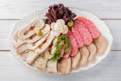 Meat plate with delicious pieces of sliced ham, sausage, olives, beef tongue, herbs and meat with radish on white plate and wooden. Table. Top view Stock Photos