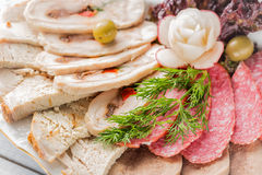 Meat plate with delicious pieces of sliced ham, sausage, olives, beef tongue, herbs and meat with radish on white plate and wooden. Table. Close up with Stock Photos