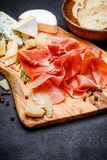 Meat plate of Italian prosciutto crudo or spanish jamon and cheese. Meat plate of Italian prosciutto crudo or spanish jamon and cheede on wooden cutting board royalty free stock photo