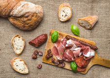 Meat plate on rustic wood board over a rough sackcloth backgroun Stock Image