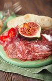 Meat platter of Cured Meat and figs on green wooden board Stock Images