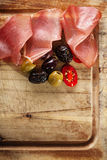Meat platter of Cured Meat and olives on old wooden board Royalty Free Stock Photography