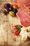 Meat platter of Cured Meat and olives on old wooden board Royalty Free Stock Photo