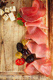 Meat platter of Cured Meat and olives on old wooden board Royalty Free Stock Photos