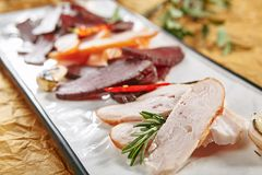 Meat Platter with Thin Slices of Cured Ham, Veal, Chicken, Pork, Beef and Sausages on White Plate royalty free stock photos