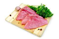 Meat pork slices with garlic. Two slices of pork, garlic, parsley, dill, pepper on a wooden board with a light shade on white background Royalty Free Stock Photo