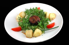 Meat with a potato and fennel. Meat with a potato on a dish on a black background royalty free stock photography