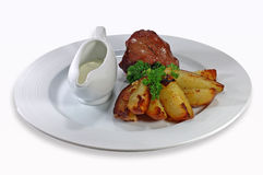 Meat with a potato and sauce. On a dish on a white background royalty free stock photography