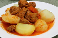 Meat with potatoes. Meat sauce with potatoes on a white plate Shallow DOF stock photos