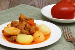 Meat with potatoes. Meat sauce with potatoes on a white plate Shallow DOF royalty free stock images