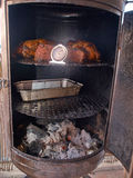 Meat prepared smoked in barbecue smoker. Meat prepared smoked in traditional cast iron barbecue smoker in backyard garden royalty free stock photo