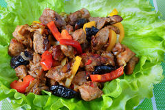 Meat with prunes and red sweet peppers. Meat stew with prunes and red sweet peppers .on green lettuce leaves Stock Images