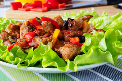 Meat with prunes and red sweet peppers . Meat stew with prunes and red sweet peppers .on green lettuce leaves.against the background of a cutting board Royalty Free Stock Photography