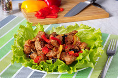 Meat with prunes and red sweet peppers . Meat stew with prunes and red sweet peppers .on green lettuce leaves.against the background of a cutting board Royalty Free Stock Image