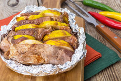 Meat with quince baking in foil in the oven Stock Photo